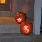 Daniel and Molly pumpkins outside lit with candles on Halloween
